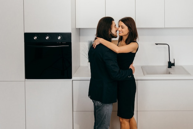Beautiful couple at home in the kitchen touching each other with their foreheads and holding hands. high quality photo