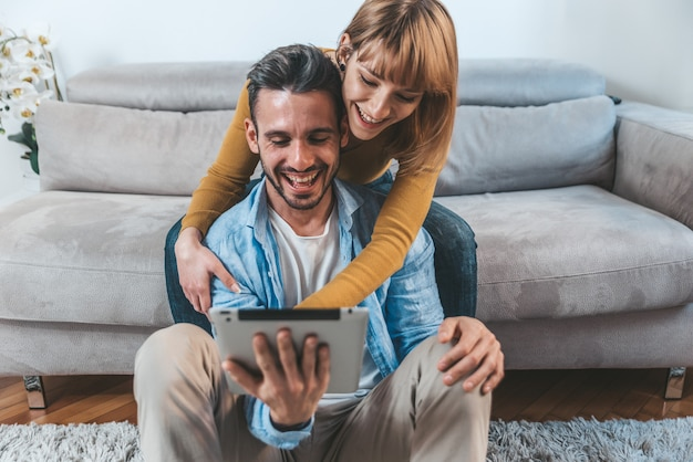 Beautiful couple at home smiling together using digital tablet pc sitting on the sofa.