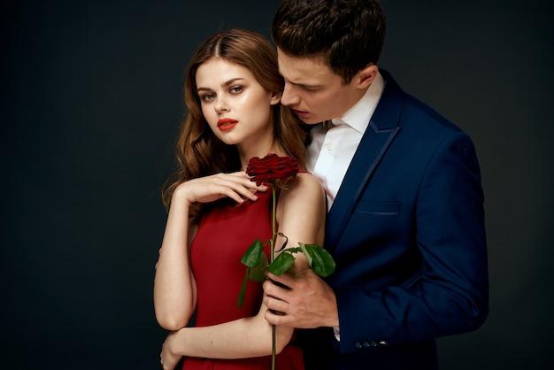 美しいカップルは暗い背景に抱擁します。
