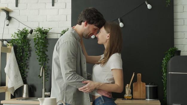 아침에 부엌에서 포옹하는 아름 다운 커플