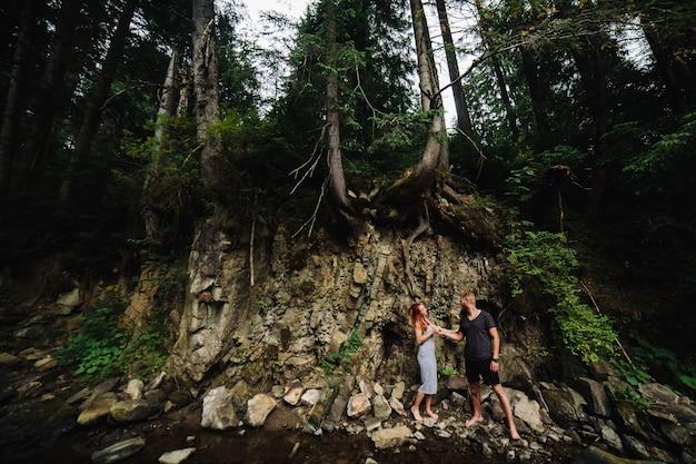 山川の近くで抱き合って美しいカップル