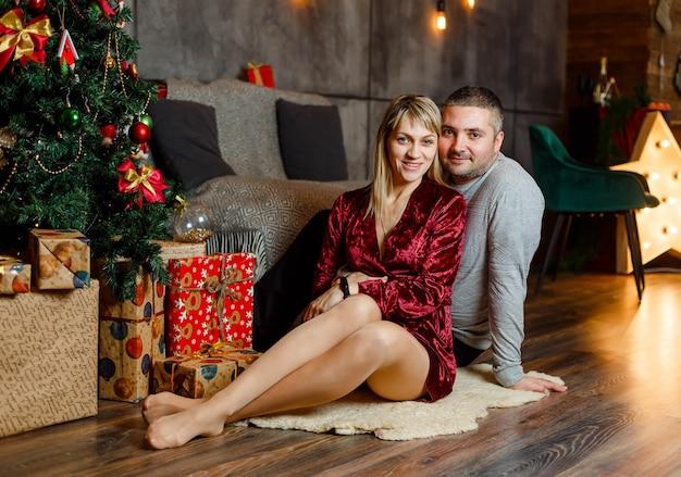 ぼやけた背景にクリスマスツリーの近くで抱き締める美しいカップル