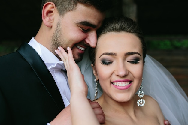 Beautiful couple hugging outdoors in wooden hut, a close angle