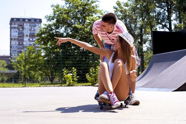 日光の下でスケートパークの美しいカップル