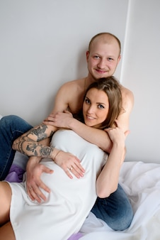 Красивая пара в ожидании ребенка, лежат в постели.