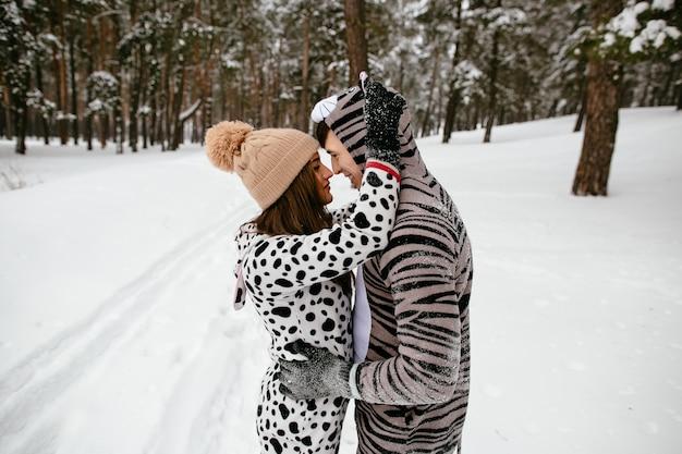動物のクールな衣装を着た美しいカップル。冬の森の中の恋人。