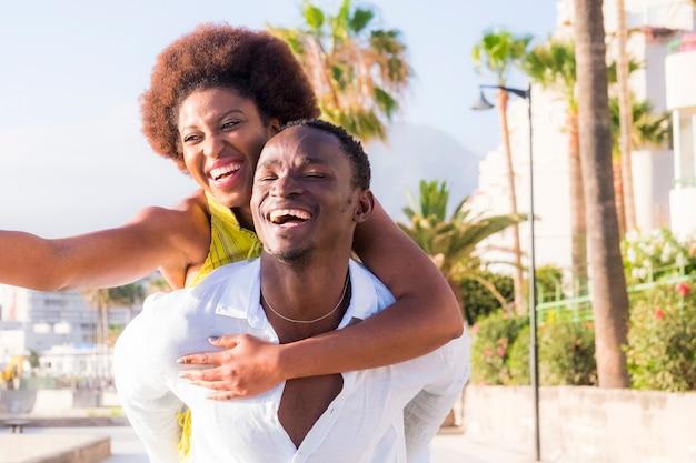 幸せな美しいカップルは、一緒に夏の時間を楽しみ、抱き合って狂ったように笑い