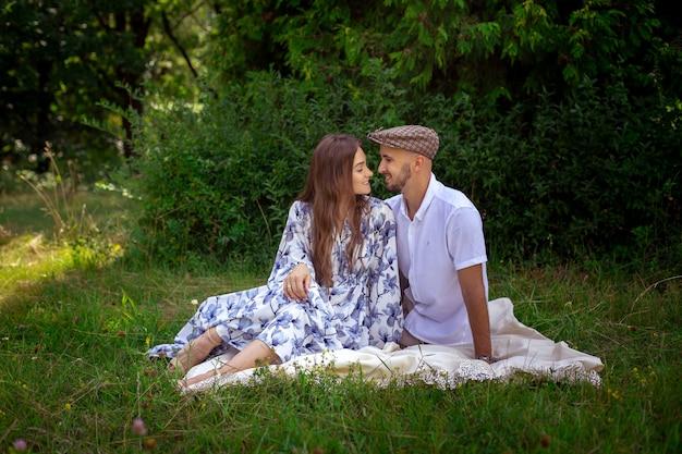 피크닉에서 사랑에 아름다운 부부는 녹색 자연에서 서로 미소