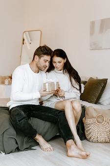 Красивая влюбленная пара обменивается подарками, сидя на диване дома, открывая коробки с романтическими подарками на день святого валентина или день рождения
