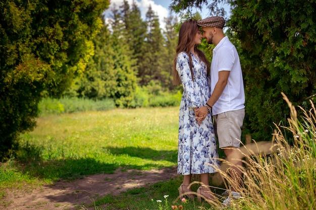 愛の美しいカップルが手を取り合い、緑の庭でお互いを見合う