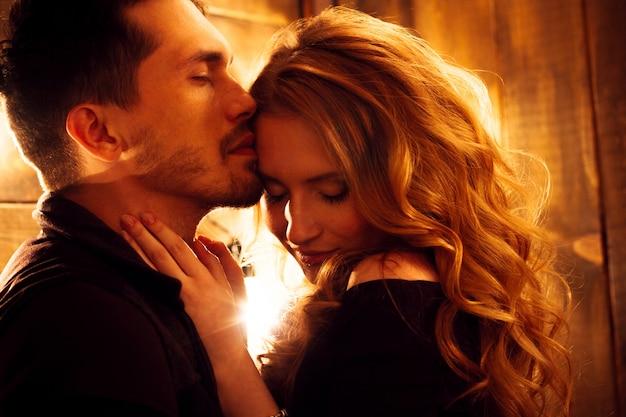 白熱灯の背景に抱いて愛の美しいカップル。