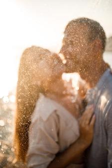 사랑에 빠진 아름다운 부부는 신혼 여행, 열대 지방에서의 휴가에 고급 스파 호텔의 물줄기 아래에서 포옹하고 키스합니다. 선택적 초점