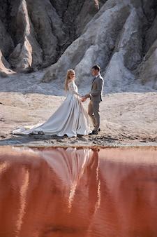 素晴らしい風景、自然の中での結婚式の愛の美しいカップルは、キスと抱擁が大好きです。