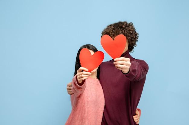 Красивая влюбленная пара на синей стене студии