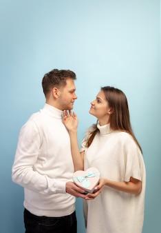 青いスタジオの壁に恋をしている美しいカップル