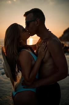바다에서 일몰을 배경으로 사랑에 빠진 아름다운 커플. 해질녘 바다에서 포옹하는 젊은 여자와 남자
