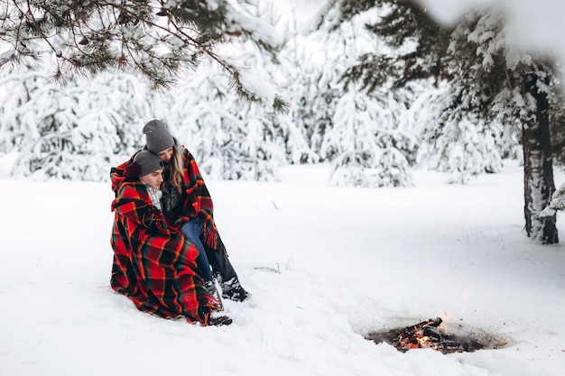 愛する美しいカップルは、毛布で覆われた冬の雪に覆われた森の火のそばに座っています