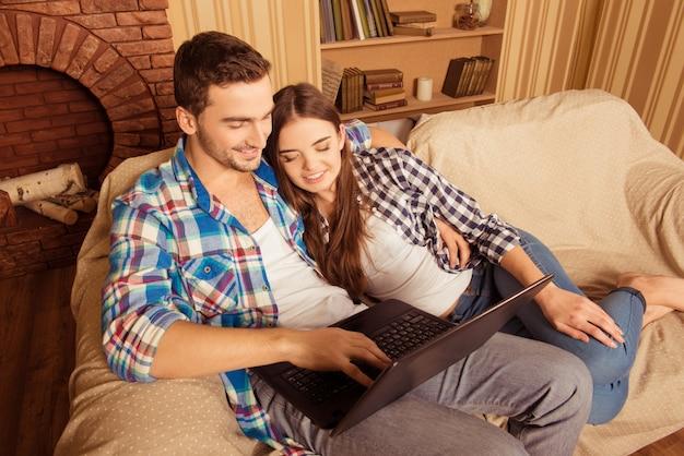 Красивая влюбленная пара сидит на диване с ноутбуком и улыбается