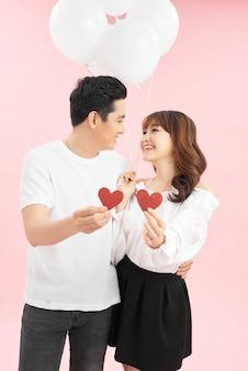 バレンタインデーのハートの形を保持している赤い風船と恋に美しいカップル