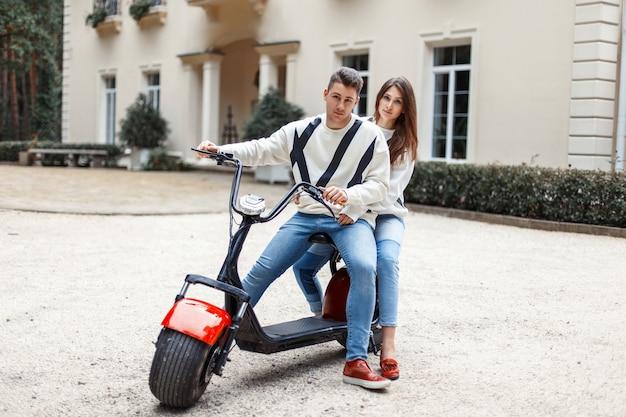 호텔 근처에서 전자 자전거를 타는 세련된 패션 의류와 사랑에 빠진 아름다운 커플