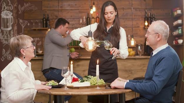 레스토랑에서 저녁 식사를 하는 60대의 아름다운 커플. 바텐더가 와인을 붓는다. 신선한 포도입니다.