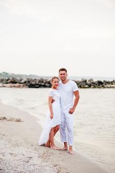 Красивая пара в белой одежде гуляет по морю