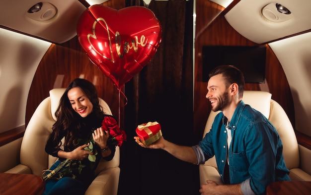 A beautiful couple is celebrating st valentineãƒâƒã'âƒãƒâ'ã'â¢ãƒâƒã'â'ãƒâ'ã'â€ãƒâƒã'â'ãƒâ'ã'â™s day on a private jet. a man is giving a present in a red box to his girlfriend