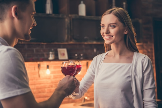 Beautiful couple is clinking glasses of wine.
