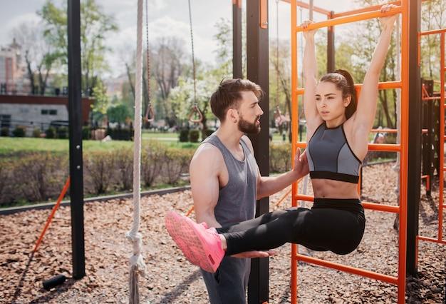 Красивая пара тренируется на улице в парке. девушка держит турник и держит ноги в горизонтальном положении к земле. парень поддерживает ее