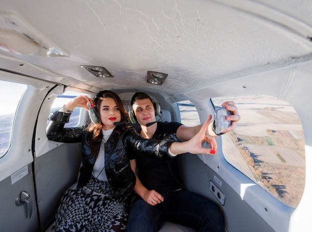 Beautiful couple is making selfie inside of helicopter with breathtaking scenery out of window