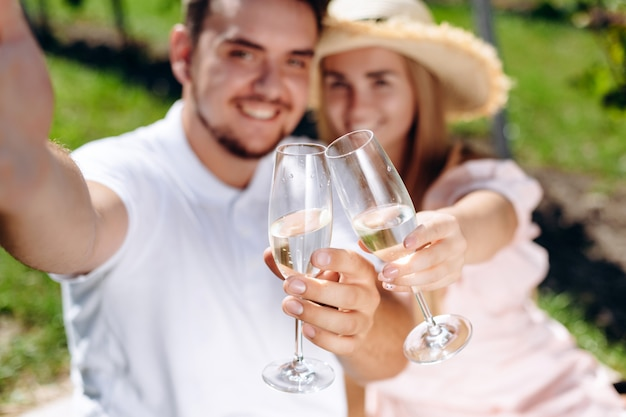 Beautiful couple is sitting on plaid holding glasses of wine and making selfies.
