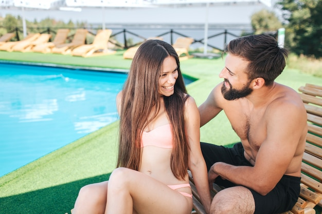 Beautiful couple is sitting on sunbeds and looking at each other. they smile. young people are near swimming pool.