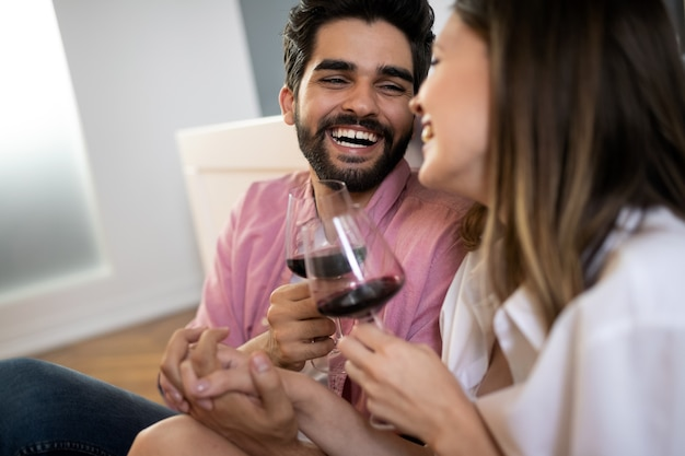 Beautiful couple is smiling, talking and hugging while spending time together in bedroom
