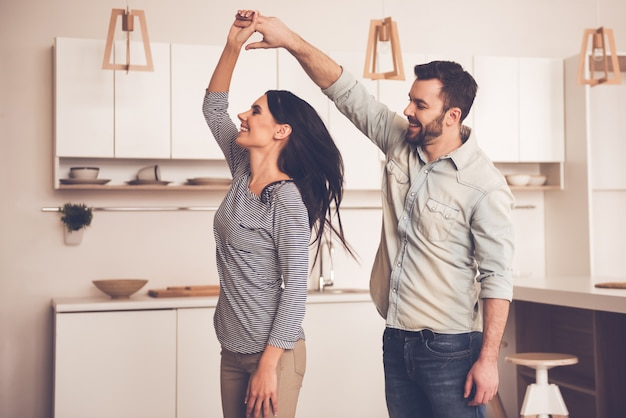 Beautiful couple is smiling while dancing in kitchen at home