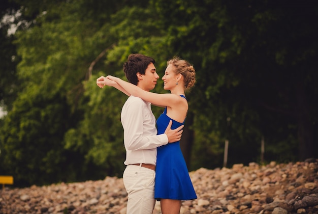 Beautiful couple is standing against a background of forests and embraces