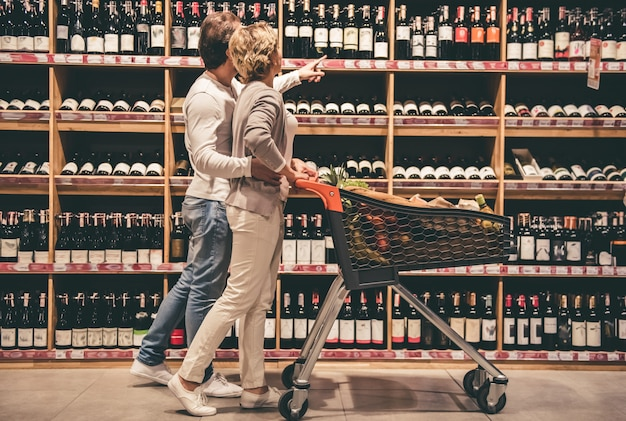 Beautiful couple is talking and smiling while choosing wine.