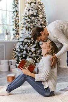 美しいカップルがギフトボックスを手に抱きしめながら一緒に新年を待っています、男はイルミネーションガーランド付きの居心地の良いリビングルームのソファで美しいクリスマスツリーの近くで彼の妻にキスします