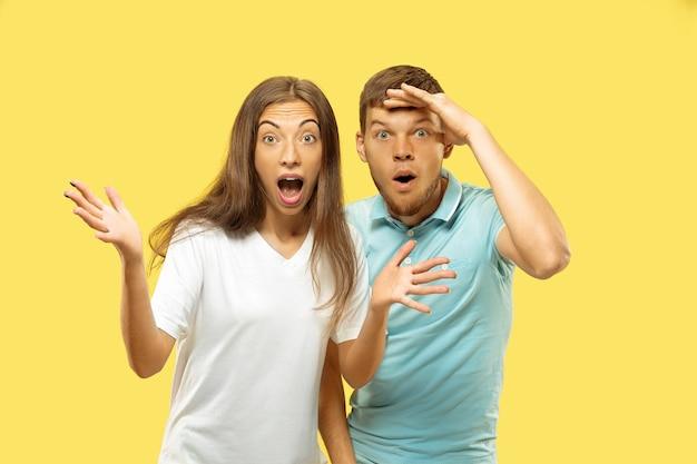 노란색 스튜디오 배경에 고립 된 아름 다운 커플