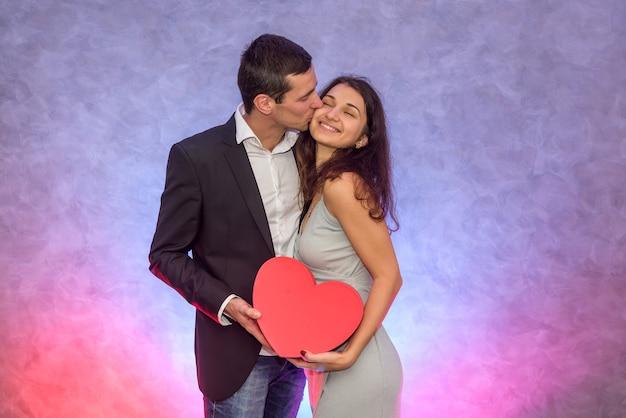 Красивая пара целуется и держит красное сердце. день святого валентина концепция
