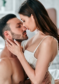 The beautiful couple kissing in the bedroom