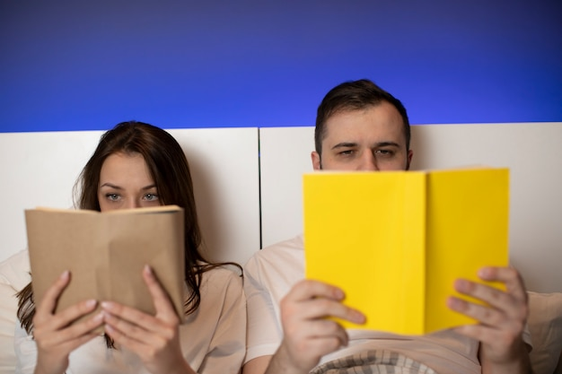美しいカップルは開いた本の後ろに隠れている手で紙の本をベッドで産む