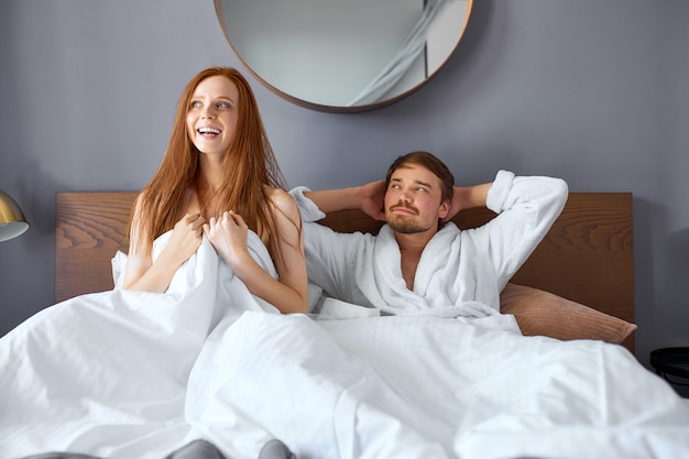 Beautiful couple lie on bed after sex, young man and woman have rest