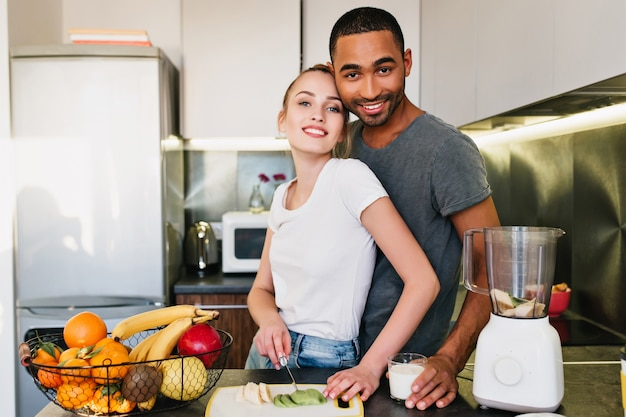 아름 다운 커플을보고 웃 고입니다. 남편과 아내가 함께 부엌에서 요리를하고 있습니다. 금발은 과일을 자릅니다. 행복한 얼굴의 티셔츠를 입은 연인들은 집에서 함께 시간을 보냅니다.