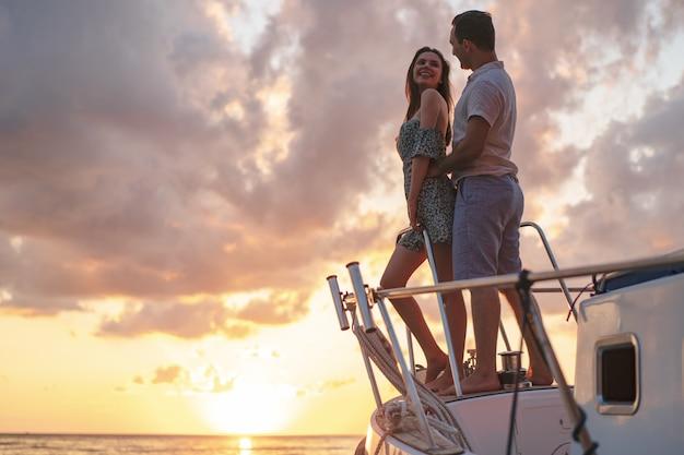요트에서 일몰을 바라보는 아름다운 커플