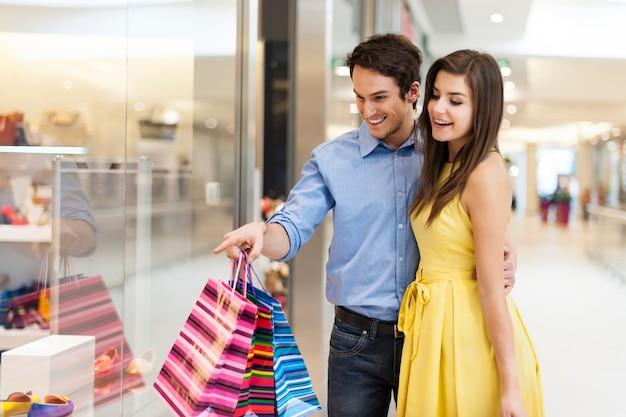 ウィンドウショッピングを見ている美しいカップル