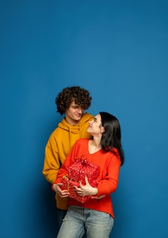 Beautiful couple in love on blue studio wall