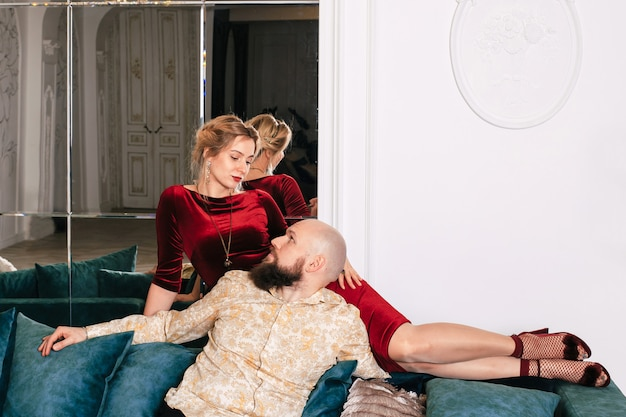 Beautiful couple in love in a bright room on the couch. a man and a woman sitting on a large sofa.