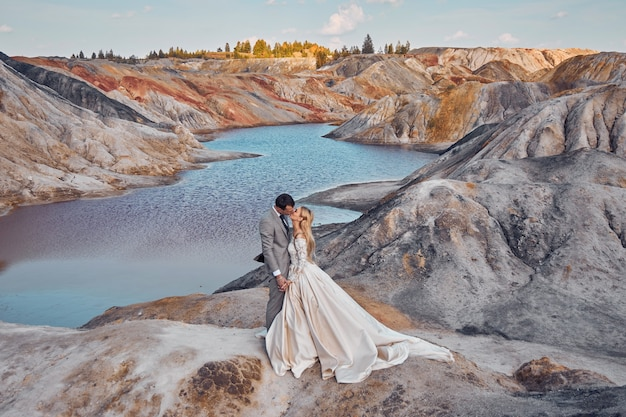 Beautiful couple in love on a fabulous landscape, wedding in nature, love kiss and hug
