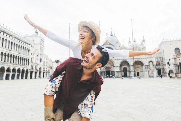Beautiful couple in love having fun embracing and laughing doing piggyback ride at holiday in venice, italy on piazza san marco.