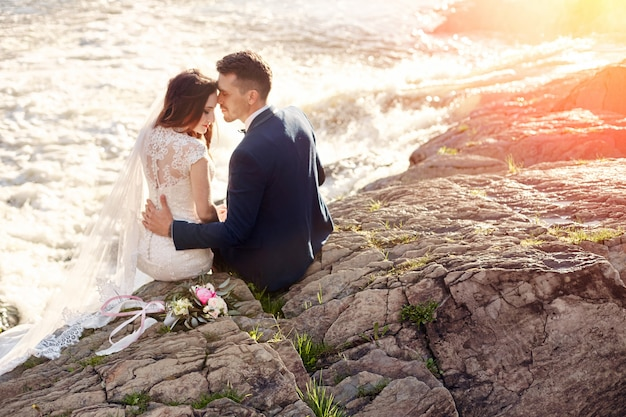 Beautiful couple love kiss while sitting on rocks